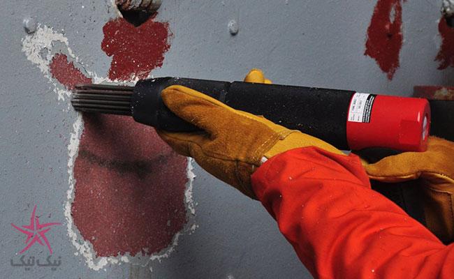 تراشیدن رنگ کهنه و یا زنگ زدگی با ابزاری به نام تفنگ سوزن